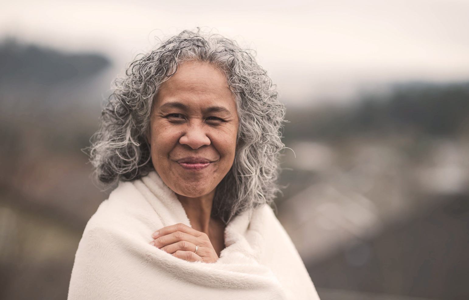 woman with gray hair in blanket, happy