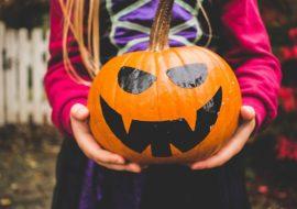 Girl in costume holding pumpkin