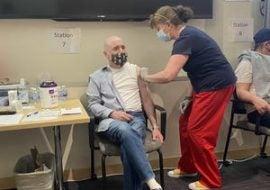 Man getting COVID vaccine with nurse