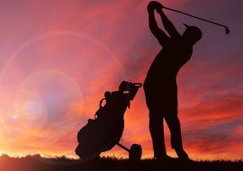 Shadow of man golfing with sunset